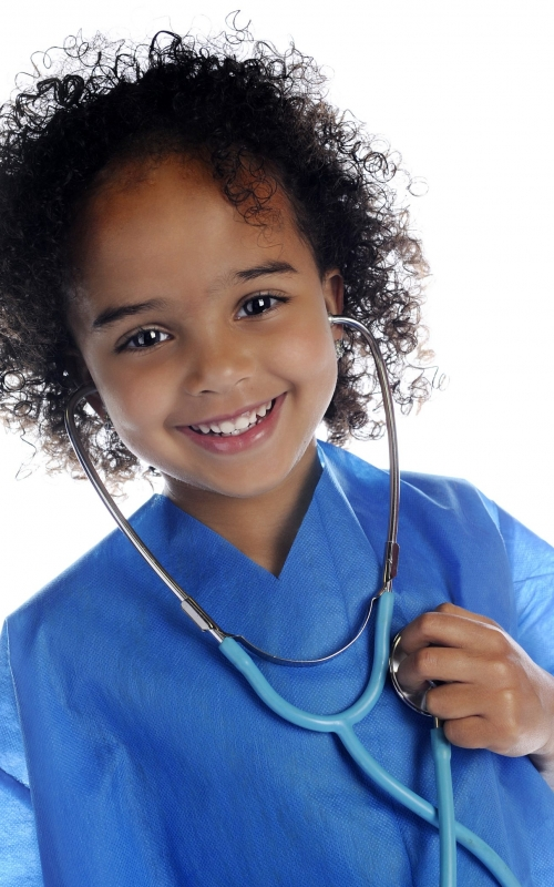 "Portrait of an adorable preschool ""docotr"" in scrubs happily listening to her own heart through a stethoscope.  On a white background."